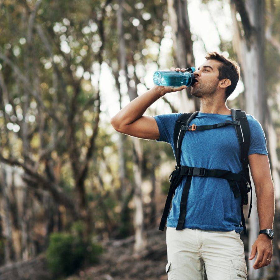 Cropped shot of a carefree young man drinking water from a bottle while going for a hike up a mountain